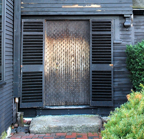 The door is composed of vertical boards on the exterior scored and studded with nails in a diamond pattern.