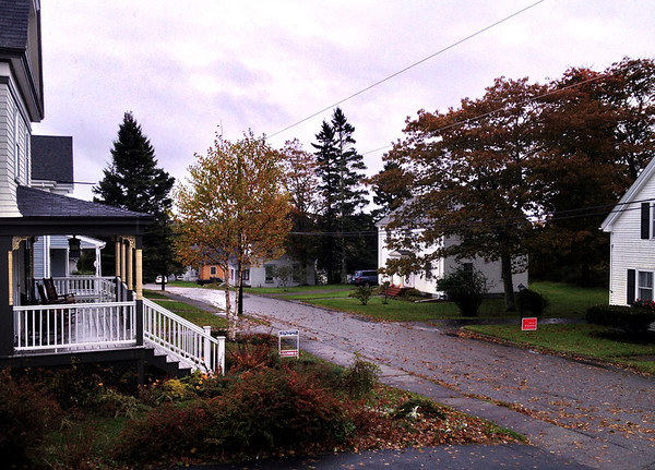 View down a rainy Summer Street in front of the Peacock House in Lubec