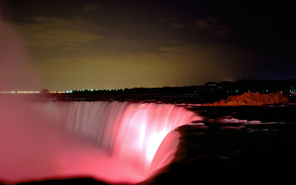Water rushed over the Canadian Falls at night.