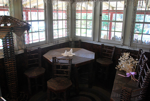 Table, chairs, lamp, and settee on the sunporch of the Paper House