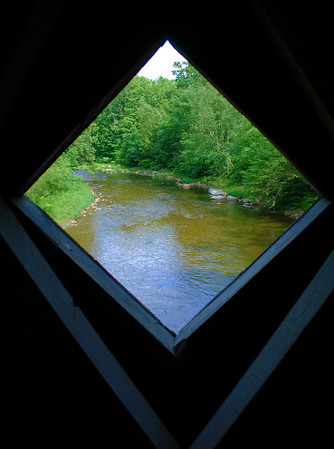 A view out of a window at the Saxton River from inside the Hall Covered Bridge.