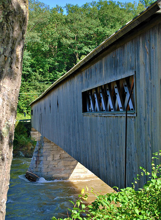 A side view of the West Dummerston Covered Bridge in Vermont.